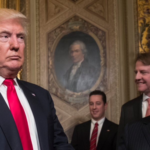 President Donald Trump leaves the President's Room of the Senate at the Capitol after he formally signed his cabinet nominations into law, in Washington, Jan. 20, 2017. At far right is Chief of Staff Reince Priebus, with White House counsel Donald McGahn, second from right. (Credit: J. Scott Applewhite - Pool/Getty Images)