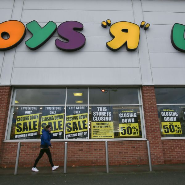"""A customer walks outside a Toys """"R"""" Us store with """"closing down sale"""" signs in the windows in south London on Feb. 9, 2018. (Credit: DANIEL LEAL-OLIVAS/AFP/Getty Images)"""