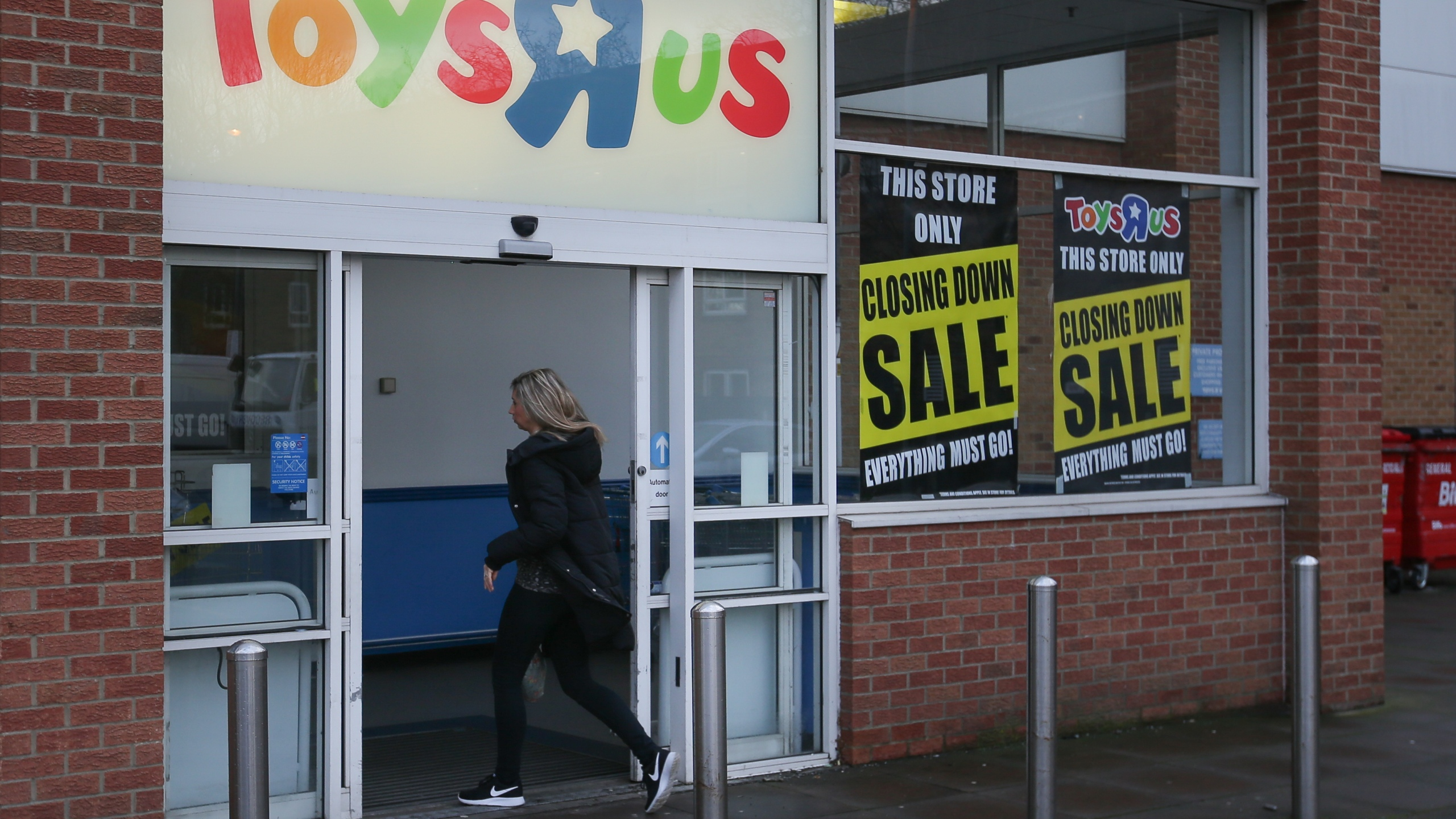 A customer walks inside a Toys 'R' Us store with 'closing down sale' signs in the windows in south London on February 9, 2018. (Credit: DANIEL LEAL-OLIVAS/AFP/Getty Images)