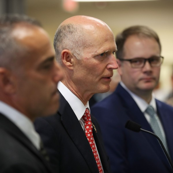 Florida Governor Rick Scott (center) stands with Andy Pollack (left) who lost his daughter Meadow Pollack, 18, and Ryan Petty who lost his daughter Alaina Petty,14, during the mass shooting at Marjory Stoneman Douglas High School, as they attend a press conference at Miami-Dade police headquarters on Feb. 27, 2018 in Doral, Florida. (Credit: Joe Raedle/Getty Images)