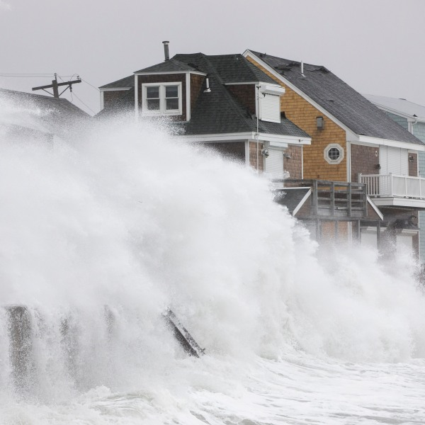 Waves crash over houses as a large coastal storm hits Scituate, Massachusetts on March 2, 2018. (Credit: Scott Eisen/Getty Images)