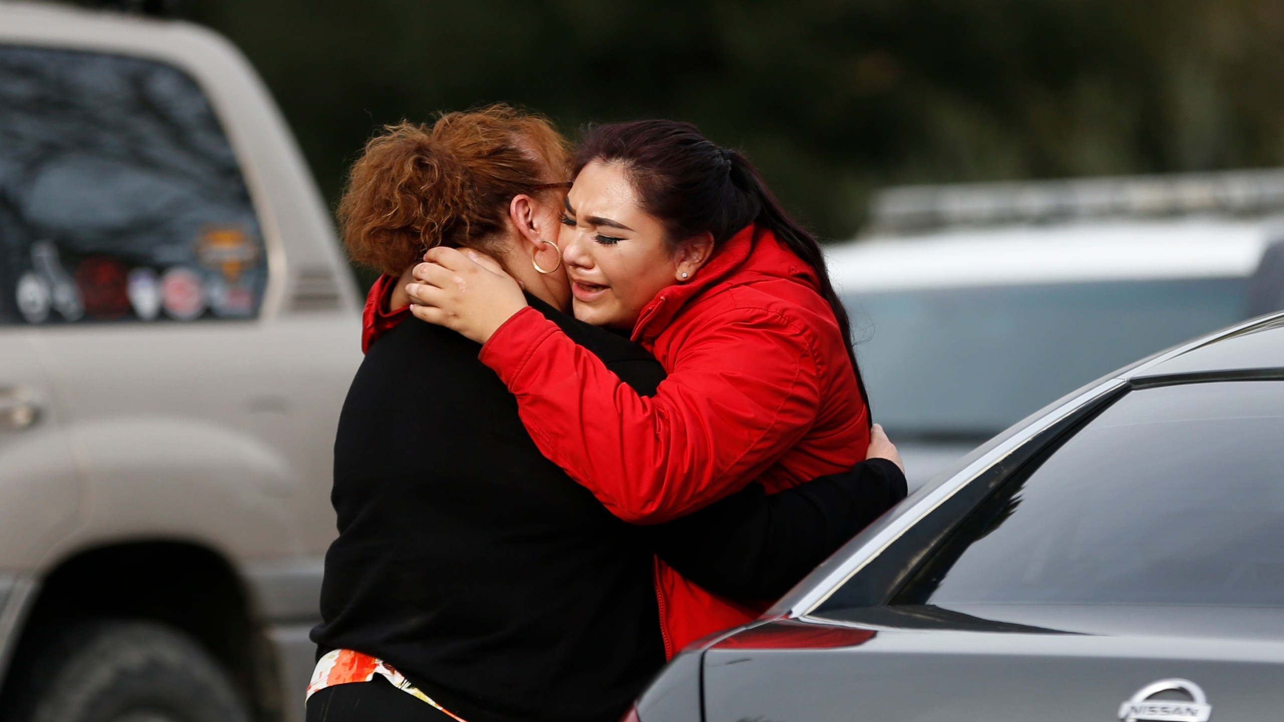 Vanessa Flores, right, embraces another woman after she leaves the locked down Veterans Home of California during an active shooter turned hostage situation on March 9, 2018, in Yountville, California. (Credit: Stephen Lam / Getty Images)