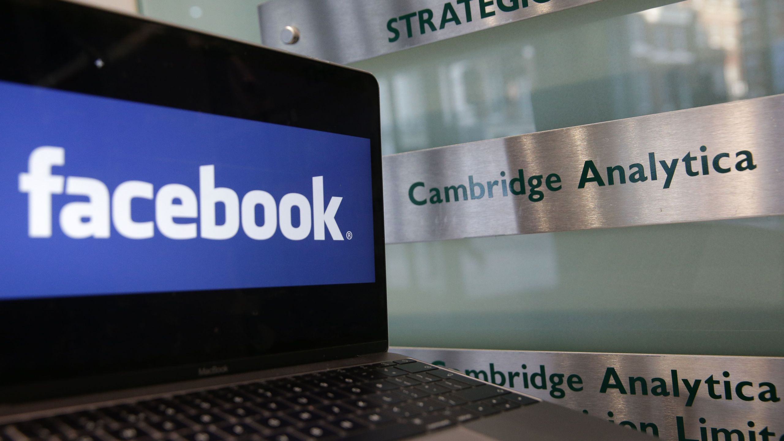 A laptop showing the Facebook logo is held alongside a Cambridge Analytica sign at the entrance to the building housing the offices of Cambridge Analytica in central London on March 21, 2018. (Credit: Daniel Leal-Olivas / AFP / Getty Images)