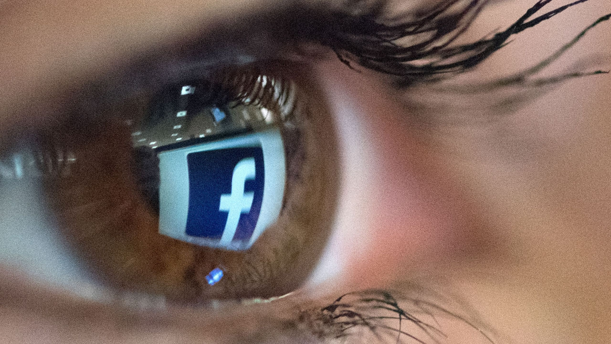 An illustration picture taken on March 22, 2018, in Paris shows a close-up of the Facebook logo in the eye of an AFP staff member posing while she looks at a flipped logo of Facebook. (Credit: Christophe Simon / AFP / Getty Images)