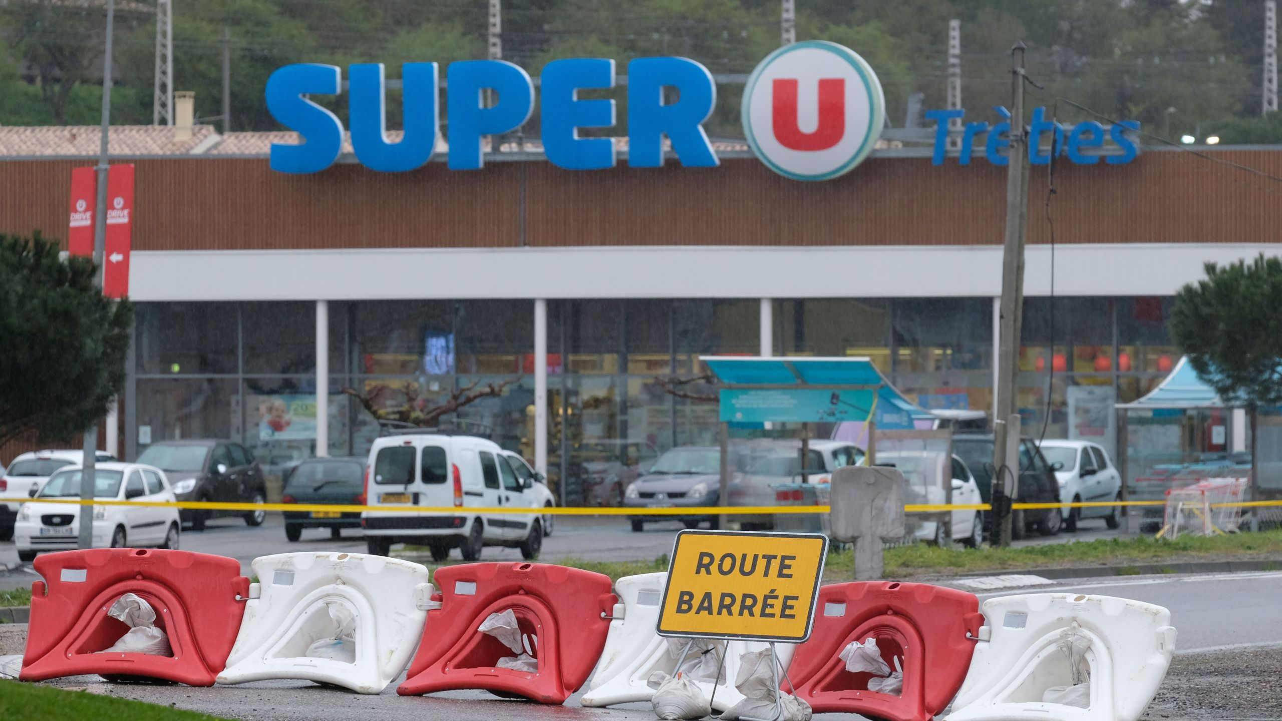"""This picture taken in the town of Trebes, southwestern France on March 24, 2018 shows a sign reading """"Closed road"""" at the entrance of the Super U supermarket where a gunman took hostages in a string of attacks that left a total of four people dead. (Credit: Eric Cabanis/AFP/Getty Images)"""