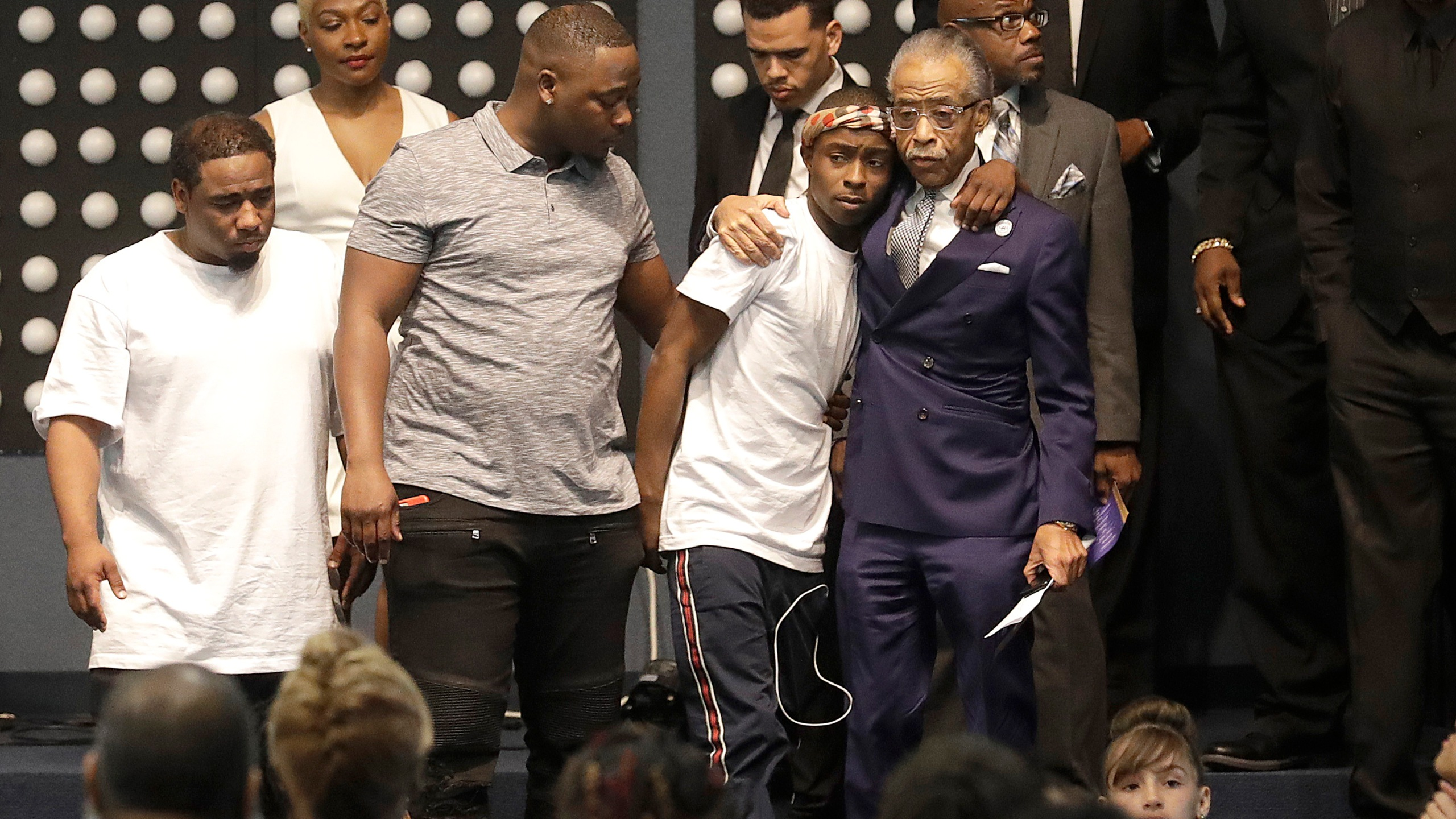 Rev. Al Sharpton, center right, hugs Stevante Clark during the funeral services for his brother, Stephon Clark, at Bayside Of South Sacramento Church on March 29, 2018. (Credit: Jeff Chiu-Pool/Getty Images)