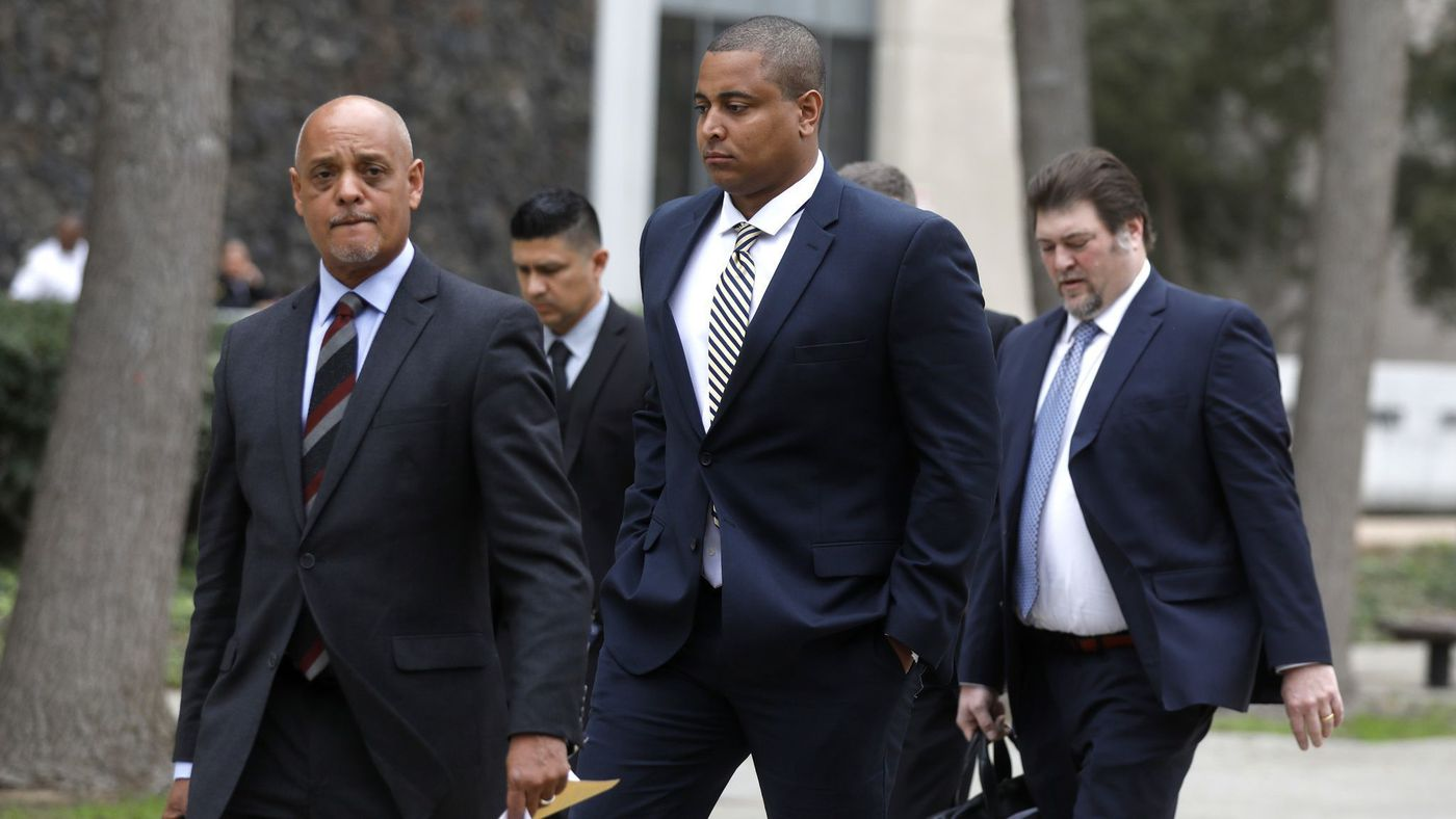 Jonathan Martin, center, walks with his attorney Winston McKesson, left, to be booked at the Los Angeles Police Department after pleading not guilty to making criminal threats at the Van Nuys Courthouse on March 20, 2018. (Credit: Gary Coronado / Los Angeles Times)