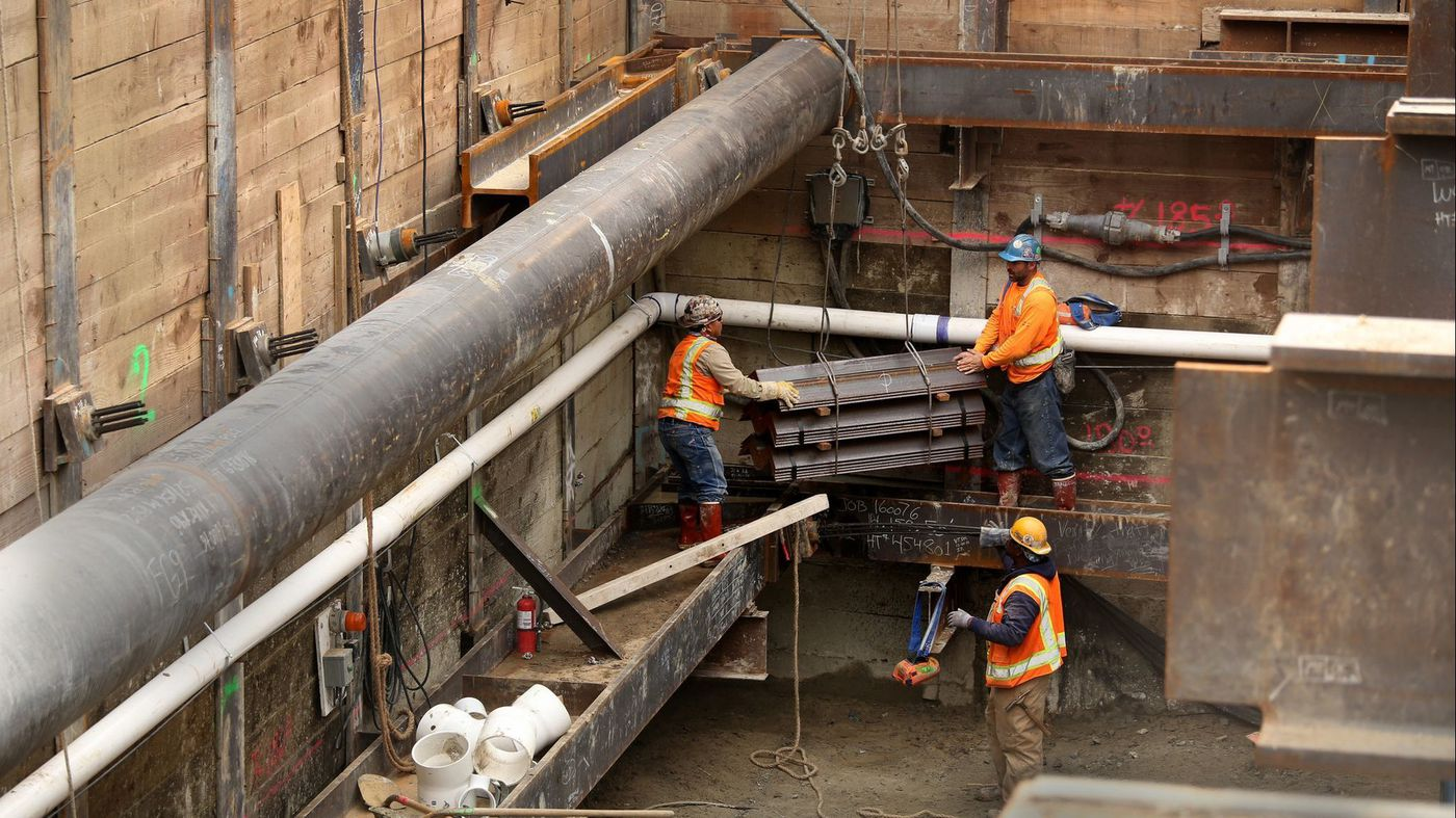 Crews work on an extension of the Metro Purple Line subway at Wilshire Boulevard and La Brea Avenue. A California bill would allow four- to eight-story residential buildings to go up on properties that sit near rail stations and major bus stops. (Credit: Glenn Koenig / Los Angeles Times)