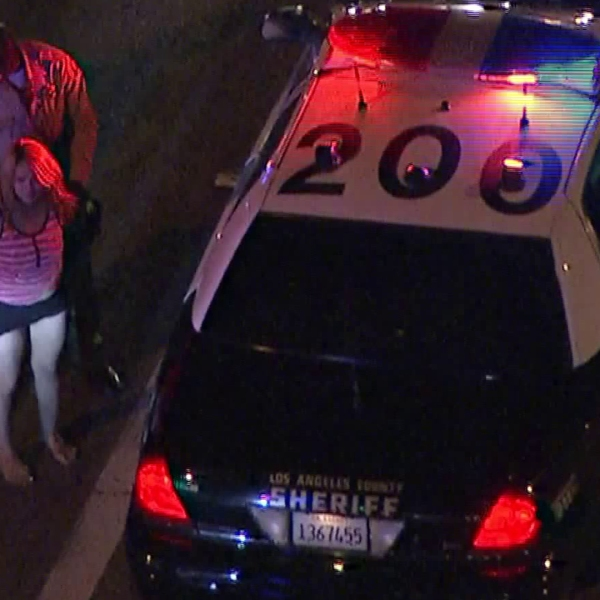 A woman is seen being handcuffed at the scene where a car crashed in the city of Industry following a pursuit earlier on March 27, 2018. (Credit: KTLA)
