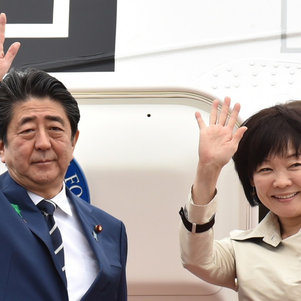 Japan's Prime Minister Shinzo Abe and his wife Akie wave as they depart for the U.S. from Tokyo's Haneda airport on April 17, 2018. (Credit Kazuhiro Nogi/AFP/Getty Images)