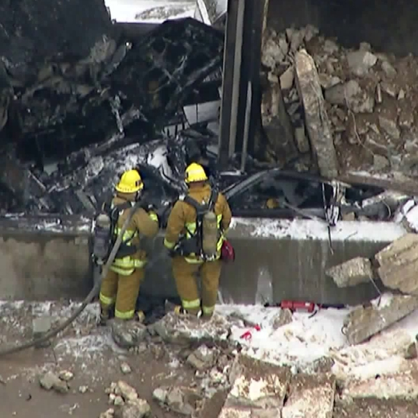 Firefighters look at a car that was crushed by an overturned big rig on the 405 Freeway in the Sepulveda Pass on April 30, 2018. (Credit: KTLA)