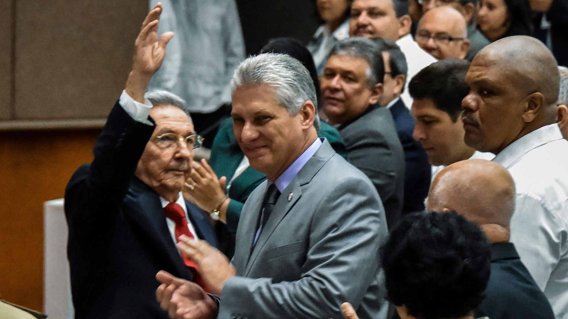 Cuban President Raul Castro (left) waves next to First Vice-President Miguel Diaz-Canel (center) during a National Assembly session that will select Cuba's Council of State ahead of the naming of a new president, in Havana on April 18, 2018. (Credit: STR/AFP/Getty Images)
