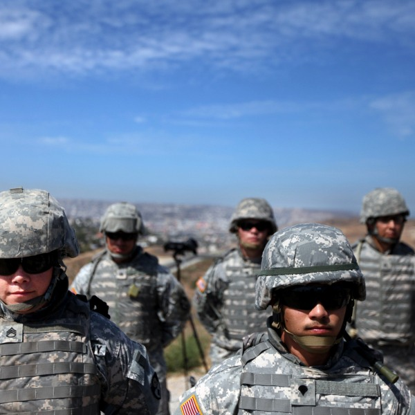 National Guard members stand along the U.S.-Mexico border in San Ysidro during a visit by then-California Gov. Arnold Schwarzenegger on Aug. 18, 2010. (Credit: Sandy Huffaker / Getty Images)