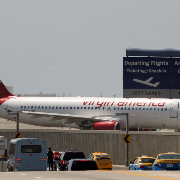 A Virgin America jet taxis into take-off position as cars enter the Los Angles International Airport on April 22, 2013. (Credit: David McNew/Getty Images)