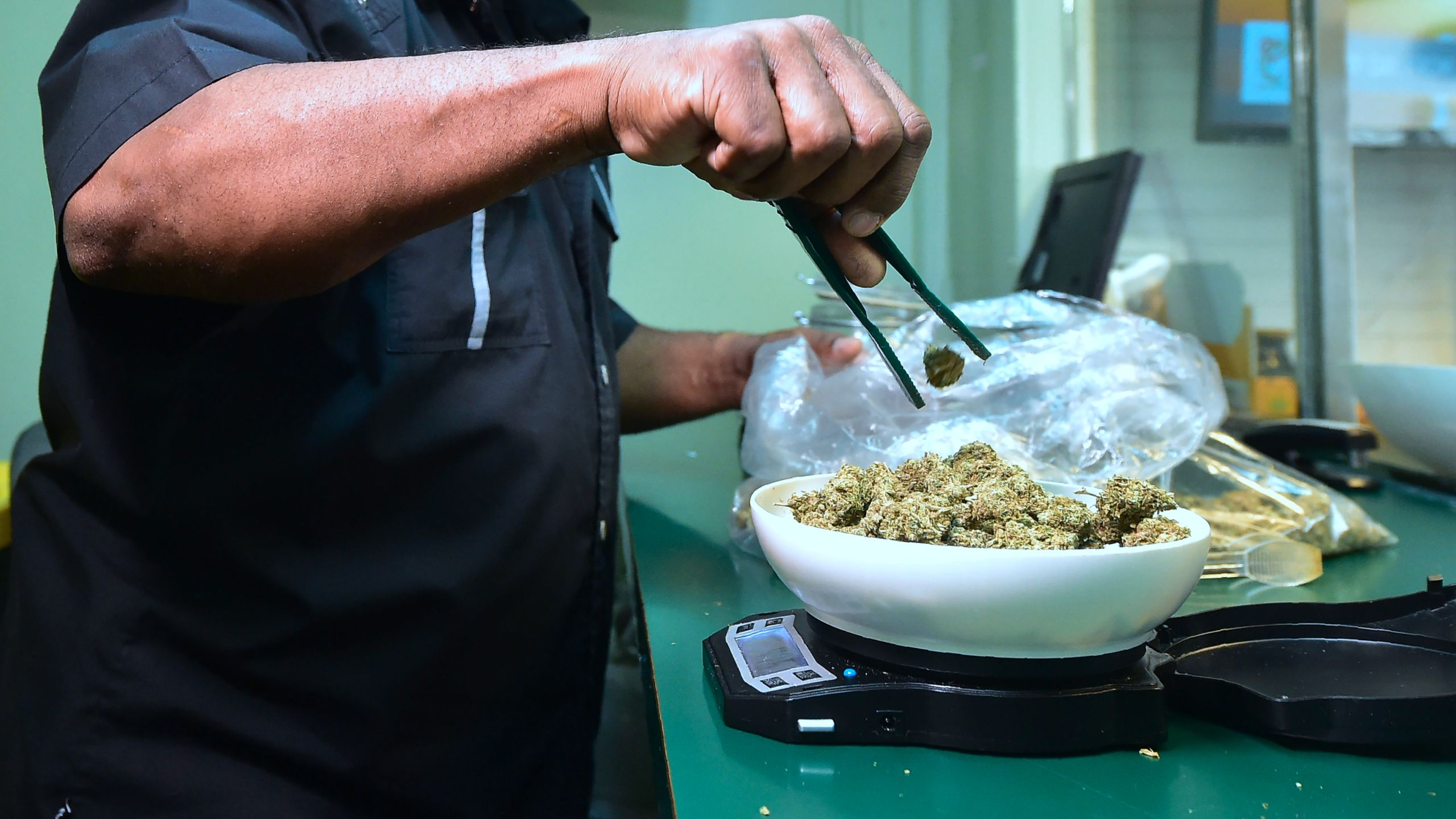 Marijuana is weighed on a scale at Virgil Grant's dispensary in Los Angeles on Feb. 8, 2018. (Credit: Frederic J. Brown / AFP / Getty Images)