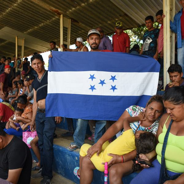 A man holds a Honduran national flag as Central Americans -taking part in a caravan called 'Migrant Viacrucis'- rest in Matias Romero, Oaxaca state, Mexico on April 2, 2018. (Credit: VICTORIA RAZO/AFP/Getty Images)
