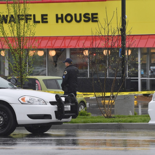 A law enforcement officer stands outside a Waffle House where four people were killed and two were wounded after a gunman opened fire with an assault weapon on April 22, 2018 in Nashville, Tennessee. (Credit: Jason Davis/Getty Images)