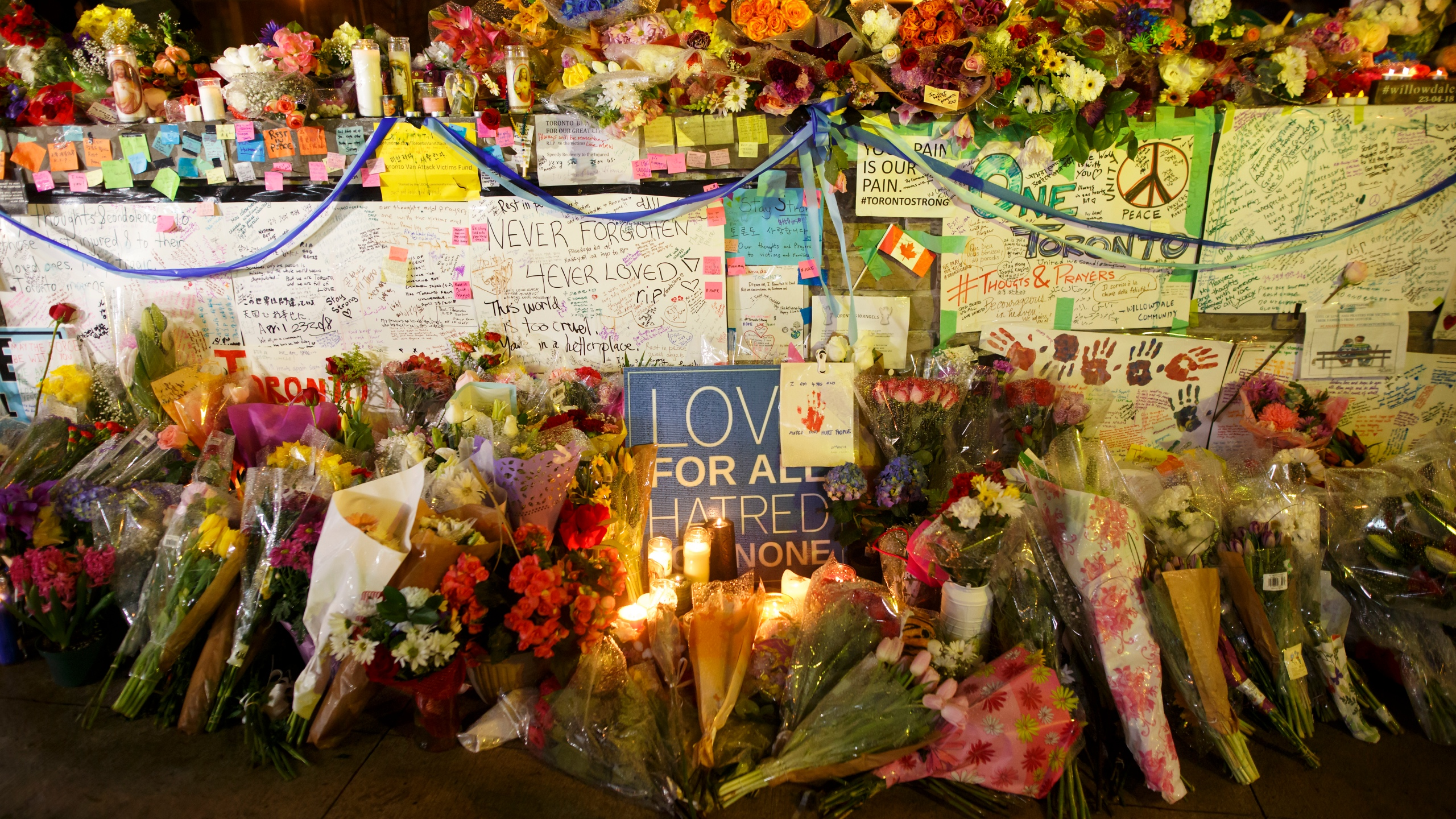 Flowers, cards, and words of sympathy adorn a makeshift memorial for victims of the mass killing on April 24, 2018 in Toronto, Canada. (Credit: Cole Burston/Getty Images)