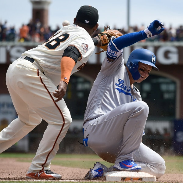 Joc Pederson of the Los Angeles Dodgers slides into third base with an RBI triple, beating the throw to Pablo Sandoval of the San Francisco Giants in the top of the second inning during game one of a doubleheader at AT&T Park on April 28, 2018 in San Francisco. (Credit: Thearon W. Henderson/Getty Images)