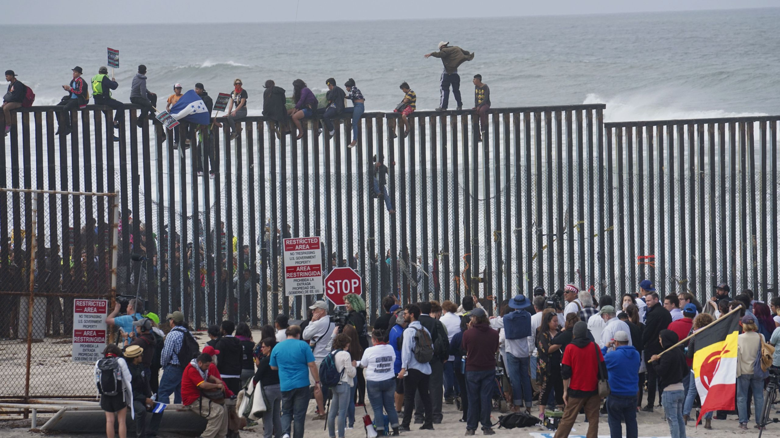 Pro-migrant caravan demonstrators climb the US-Mexico border fence during a rally on April 29, 2018 in San Ysidro. (Credit: SANDY HUFFAKER/AFP/Getty Images)