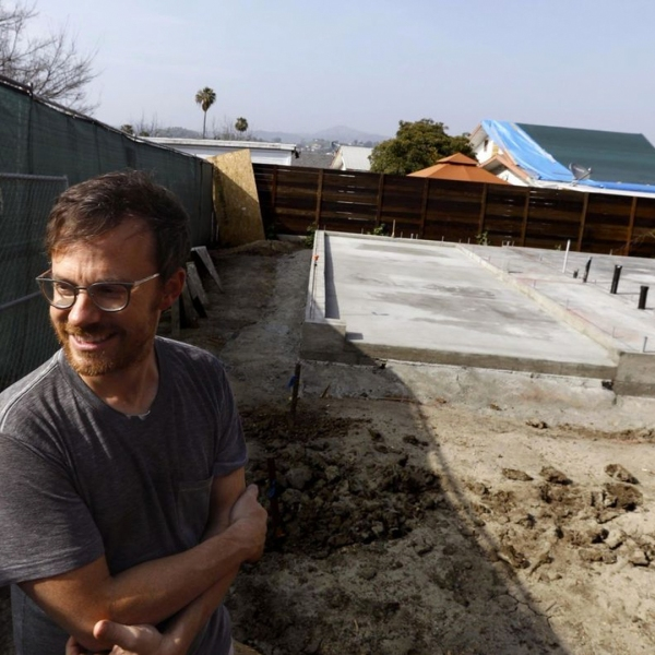 Trent Wolbe in his Highland Park backyard, where a city-sponsored second home is under construction. (Credit: Genaro Molina / Los Angeles Times)