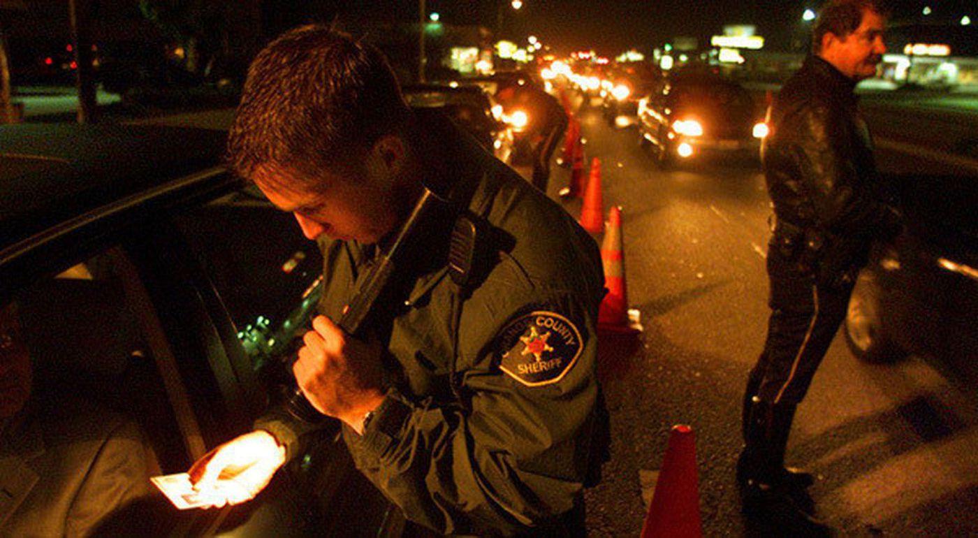 Orange County sheriff's Deputy Jeff Puckett checks a motorist's identification at a DUI checkpoint. (Credit: Al Schaben / Los Angeles Times)
