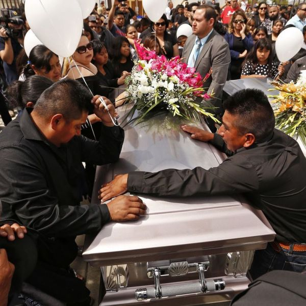 The brothers of Santos Hilario Garcia, who was killed in a crash while fleeing ICE in Kern County along with his partner, Marcelina Garcia Perfecto, are seen standing around the couple's caskets on the day of their funeral service at Our Lady of Guadalupe Church in Delano on April 2, 2018. (Credit: Al Seib / Los Angeles Times)