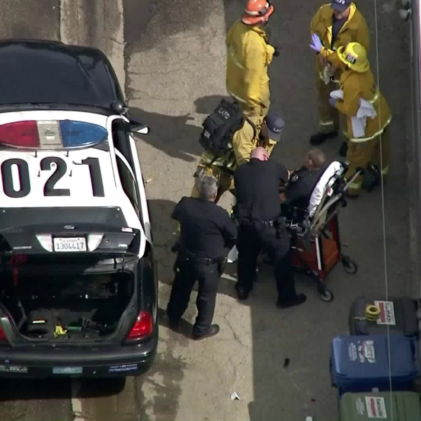 An LAPD is put on a gurney after a shooting in Reseda on April 9, 2018. (Credit: KTLA)