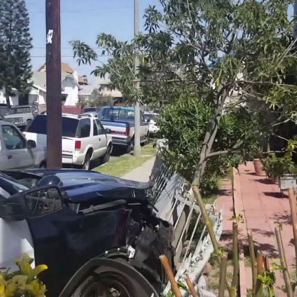 An LAPD cruiser is seen smashed into the front yard fence of a home in Vermont Square in South L.A. on April 14, 2018. (Credit: KTLA)