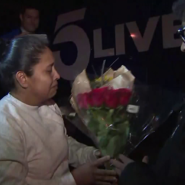 Marcelina Rios is tearful as her son Roberto hands her a bouquet of flowers upon her release from immigration detention in Adelanto on April 12, 2018. (Credit: KTLA)