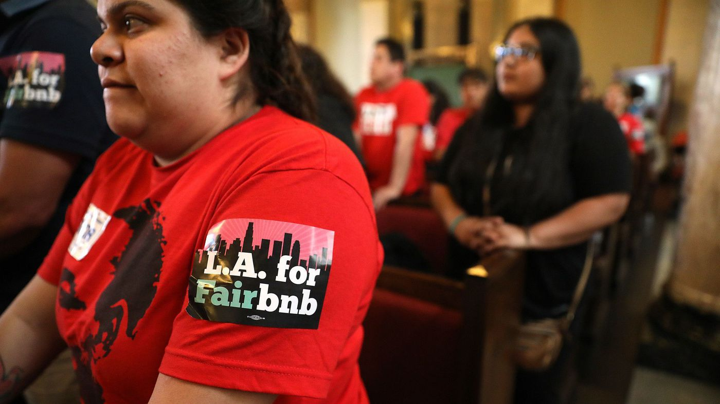 Genesis Diaz, 24, of South Los Angeles stands with others concerned about the effects of short-term rentals during a City Council committee meeting at City Hall on April 10, 2018. (Credit: Christina House / Los Angeles Times)