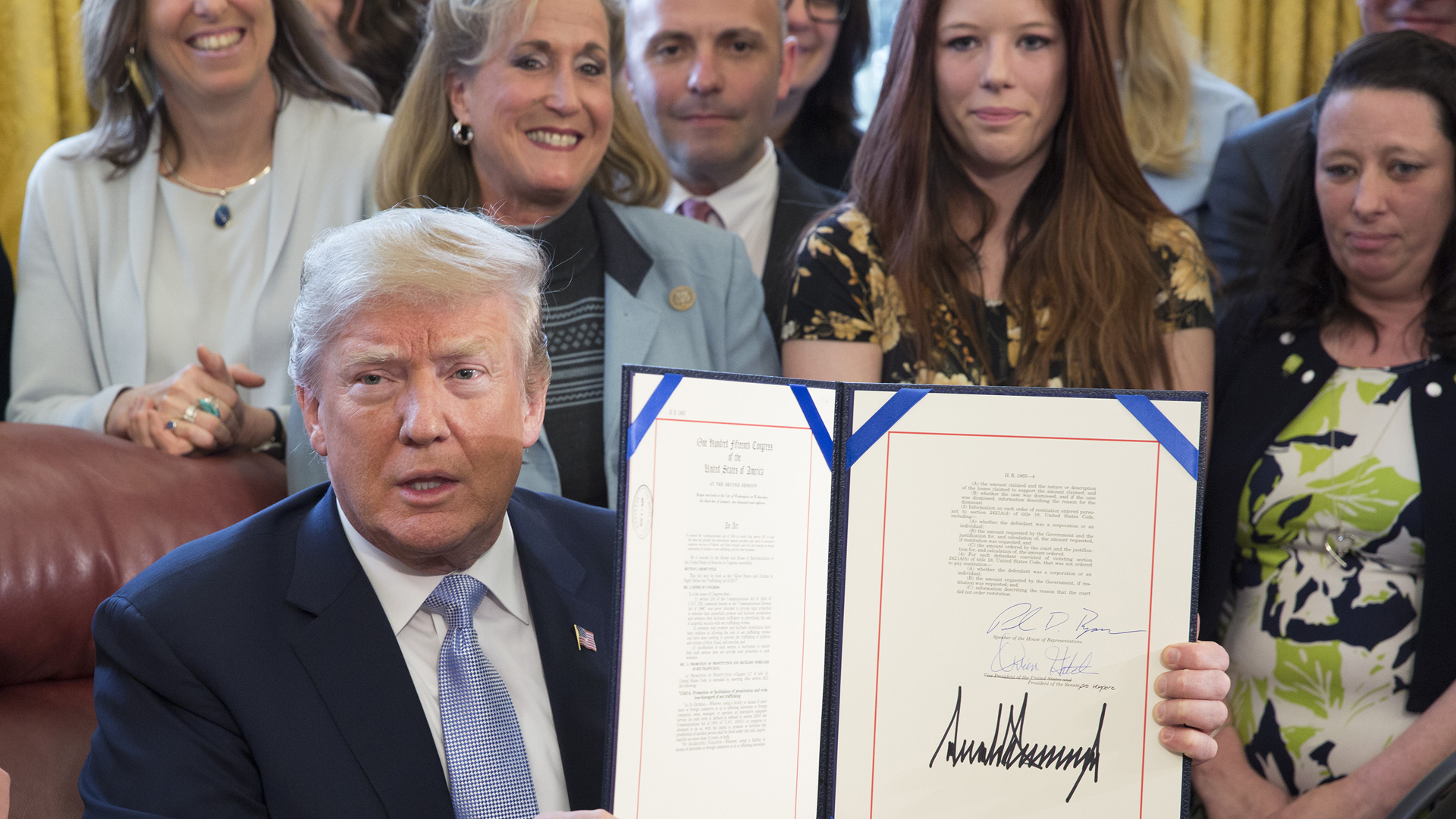 "Donald Trump displays H.R. 1865, the ""Allow States and Victims to Fight Online Sex Trafficking Act of 2017"" after signing it into law at the White House on April 11, 2018. (Credit: Chris Kleponis-Pool/Getty Images)"