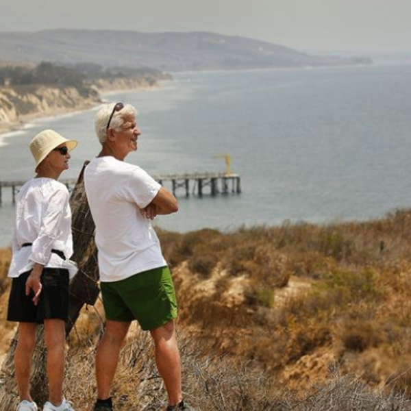 Jeff Kamer, right, of Goleta, shows Debby Kamer,his visiting sister, the view of the ocean at the entrance to Hollister Ranch. Its owners seek to block a public access attempt by the California Coastal Commission to the shoreline of the secluded ranch, which is tucked between the Santa Ynez Mountains and Pacific Ocean in this undated photo. (Credit: Al Seib / Los Angeles Times)