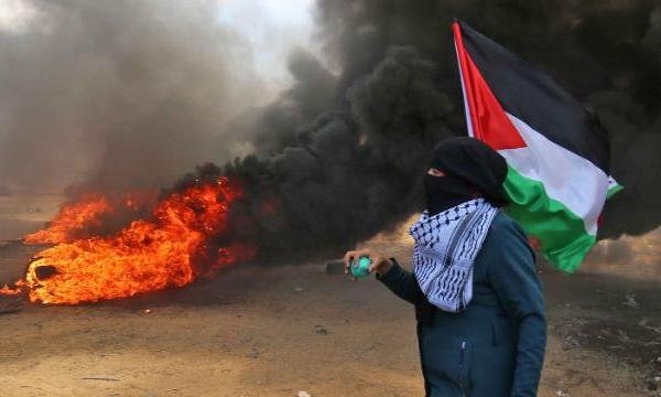 A Palestinian man holding his national flag walks in the smoke billowing from burning tires during clashes with Israeli forces along the border with the Gaza strip east of Khan Yunis on May 14, 2018. (Credit: SAID KHATIB/AFP/Getty Images)