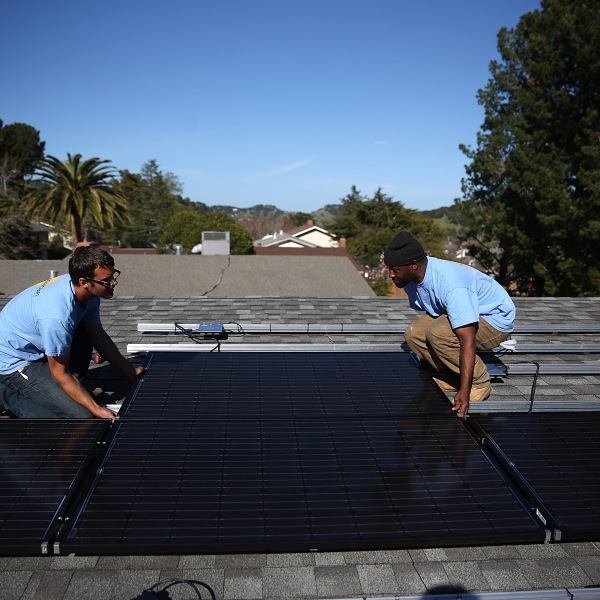 SolarCraft workers Craig Powell (left) and Edwin Neal install solar panels on the roof of a home in San Rafael, California on February 26, 2015. (Credit: Justin Sullivan/Getty Images)