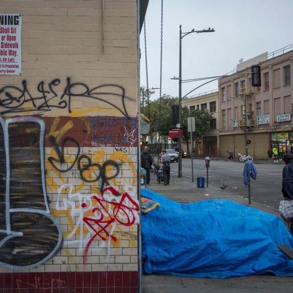 Homeless people camp on a sidewalk on Skid Row near an old sign prohibiting them from being on the sidewalk on May 1, 2017 in Los Angeles. (Credit: David McNew/Getty Images)