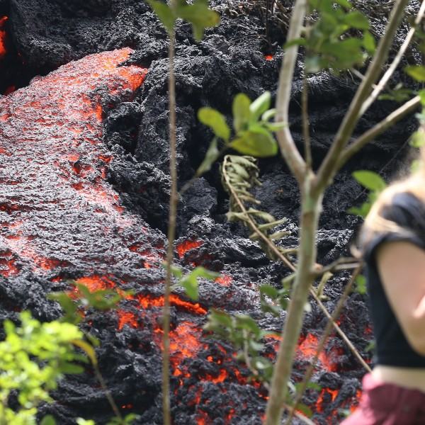 Lava flows at a new fissure in the aftermath of eruptions from the Kilauea volcano on Hawaii's Big Island as a local resident walks nearby after taking photos on May 12, 2018 in Pahoa, Hawaii. (Credit: Mario Tama/Getty Images)
