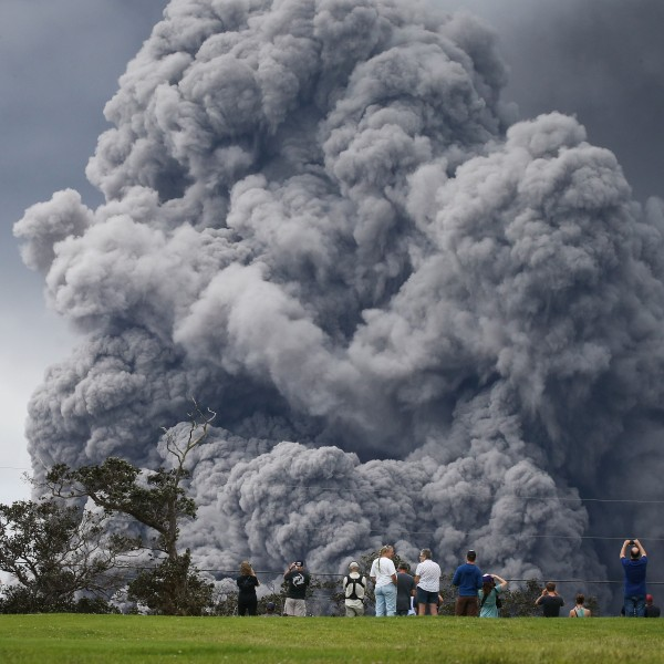 People watch at a golf course as an ash plume rises in the distance from the Kilauea volcano on Hawaii's Big Island on May 15, 2018 in Hawaii Volcanoes National Park, Hawaii. (Credit: Mario Tama/Getty Images)