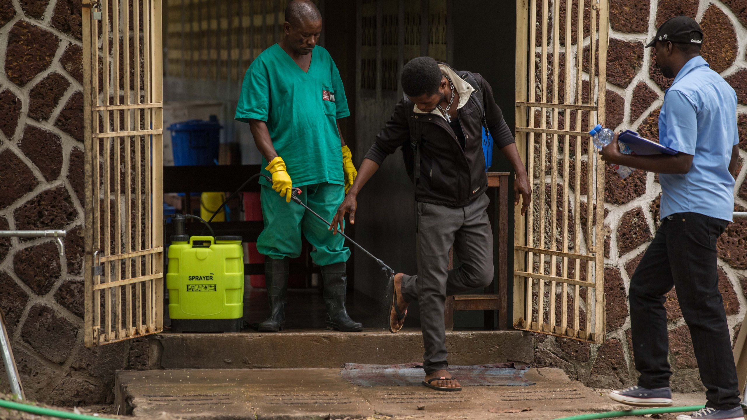 An attendant charged to handle the access to the Ebola security zone disinfects shoes outside the Wangata Reference Hospital in Mbandaka, northwest of DR Congo on May 20, 2018. (Credit: Junior Kannah/AFP/Getty Images)