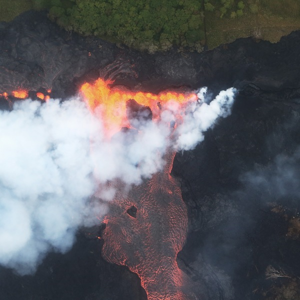 Lava erupts and flows from a Kilauea volcano fissure, toward the Pacific Ocean, on Hawaii's Big Island on May 21, 2018 near Pahoa, Hawaii. (Credit: Mario Tama/Getty Images)