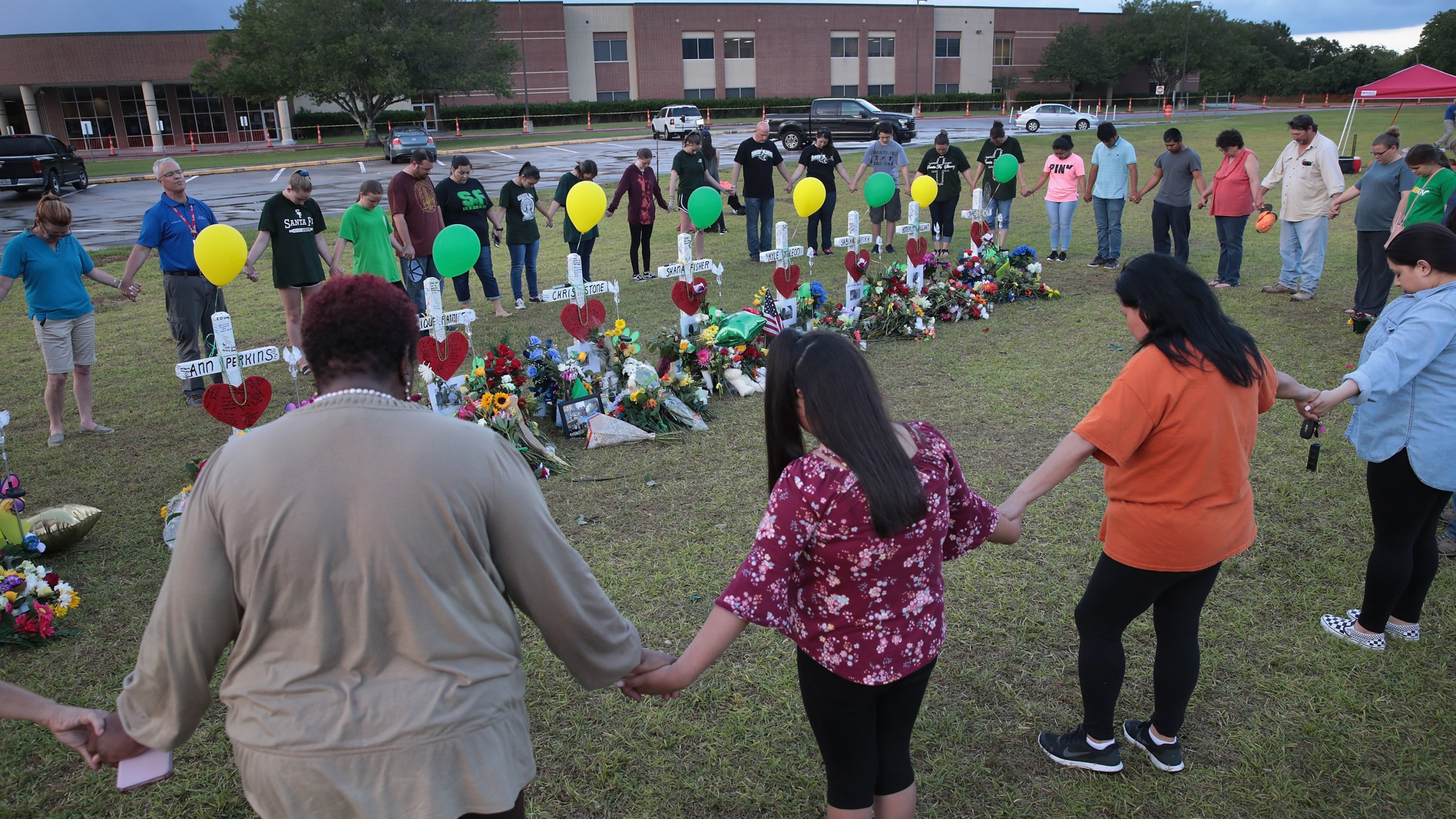 Mourners pray around a memorial in front of Santa Fe High School on May 21, 2018 in Santa Fe, Texas. (Credit: Scott Olson/Getty Images)