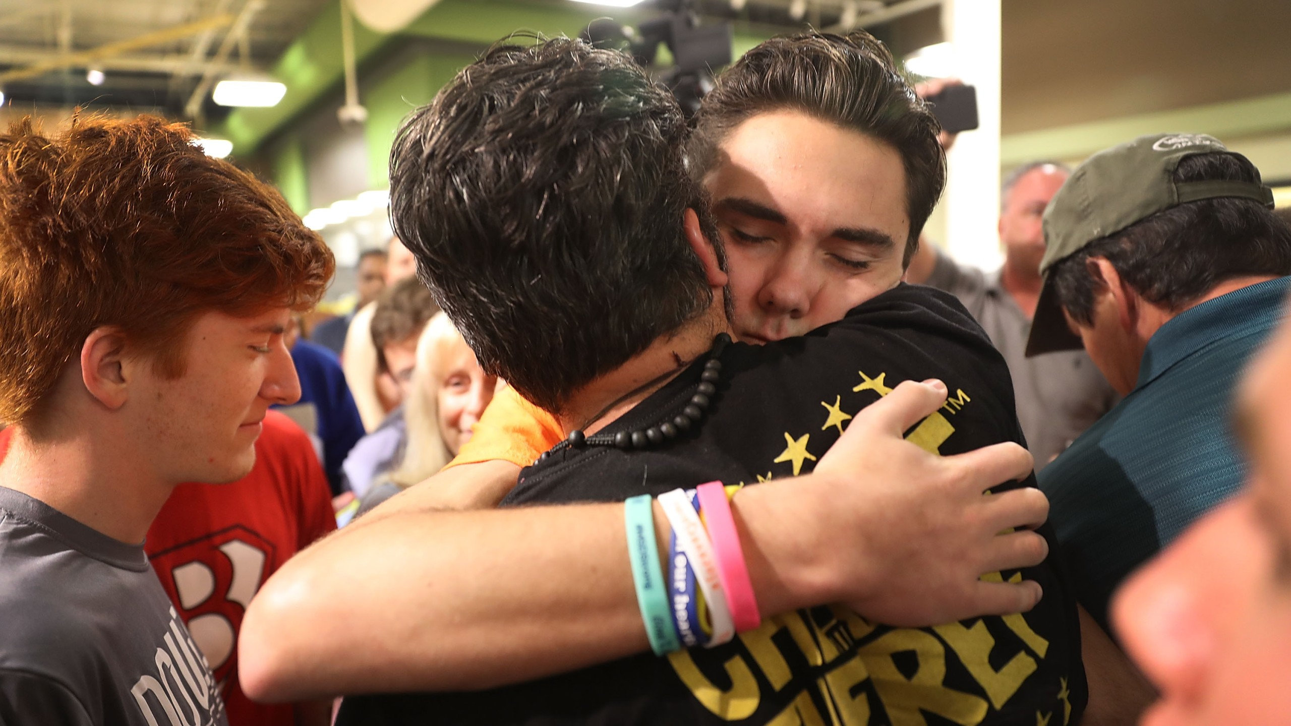 "David Hogg hugs Manuel Oliver, whose son Joaquin Oliver, was killed in the Marjory Stoneman Douglas High School mass shooting as they particpate in a ""die'-in"" protest in a Publix supermarket on May 25, 2018, in Coral Springs, Florida. (Credit: Joe Raedle/Getty Images)"