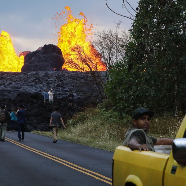 Onlookers and media gather as lava from a Kilauea volcano fissure erupts in Leilani Estates, in Pahoa on Hawaii's Big Island, May 26, 2018. (Credit: Mario Tama / Getty Images)