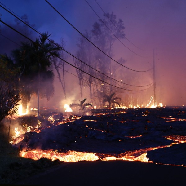 Lava from a Kilauea volcano fissure advances up a residential street in Leilani Estates, on Hawaii's Big Island, on May 27, 2018. (Credit: Mario Tama/Getty Images)