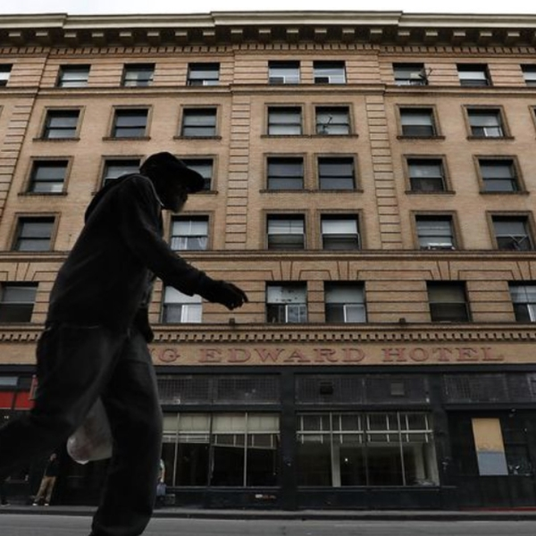 A pedestrian walks along 5th St. in downtown Los Angeles with the King Edward Hotel seen in the background. The Aids Healthcare Foundation has purchased the 106 year old hotel and plans to lease its 150 rooms to homeless people. (Credit: Mel Melcon / Los Angeles Times)