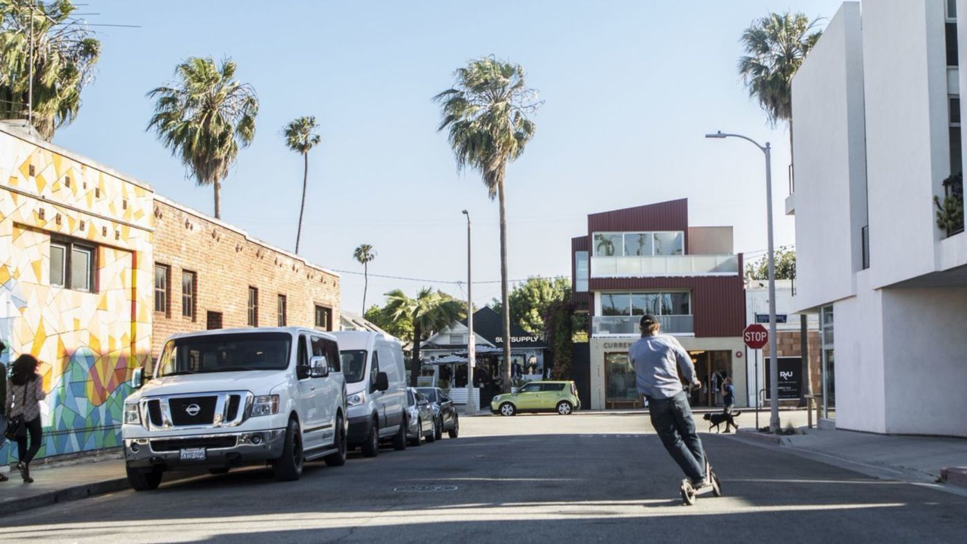 A man rides a motorized Bird scooter toward Abbott Kinney Boulevard in Venice in this undated photo. (Credit: Maria Alejandra Cardona / Los Angeles Times)