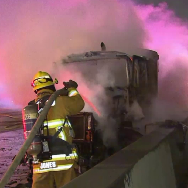 A firefighter douses flames on a big rig in Cerritos on June 16, 2018. (Credit: Loudlabs)