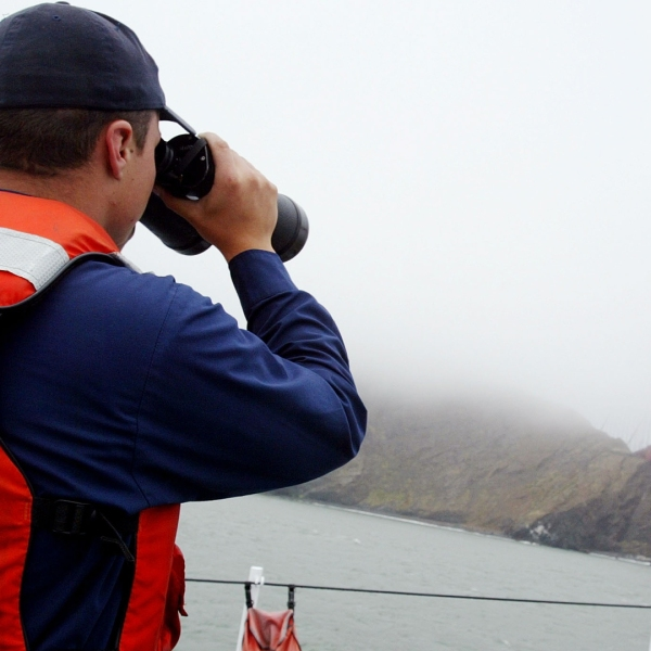 U.S. Coast Guard seaman Johnathon Baker uses binoculars to inspect the under side of the Golden Gate Bridge while on patrol aboard the USCGC Tern in the San Francisco Bay on May 23, 2003, near San Francisco. (Credit: Justin Sullivan/Getty Images)
