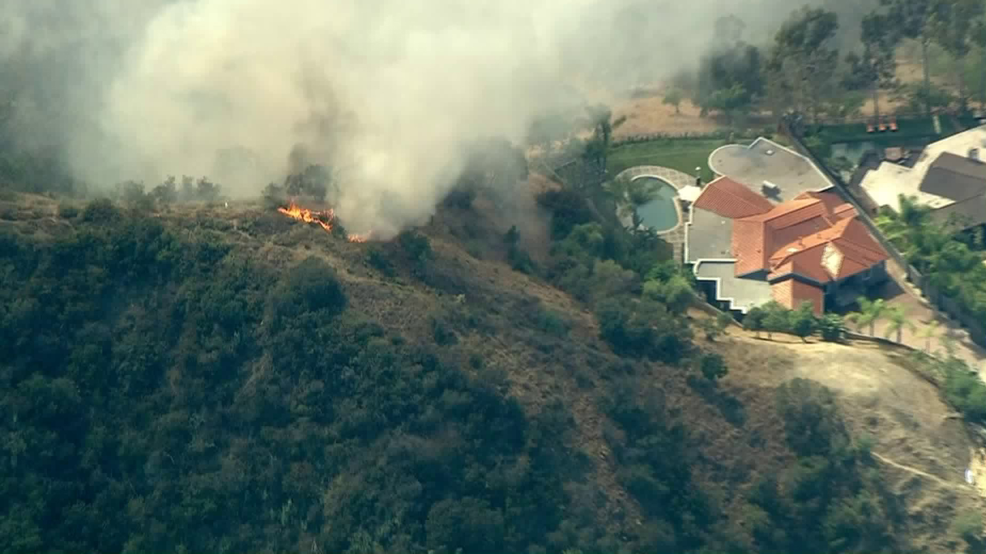 Flames burned near a home as the Portola Fire burned in the Beverly Crest area on June 12, 2018. (Credit: KTLA)