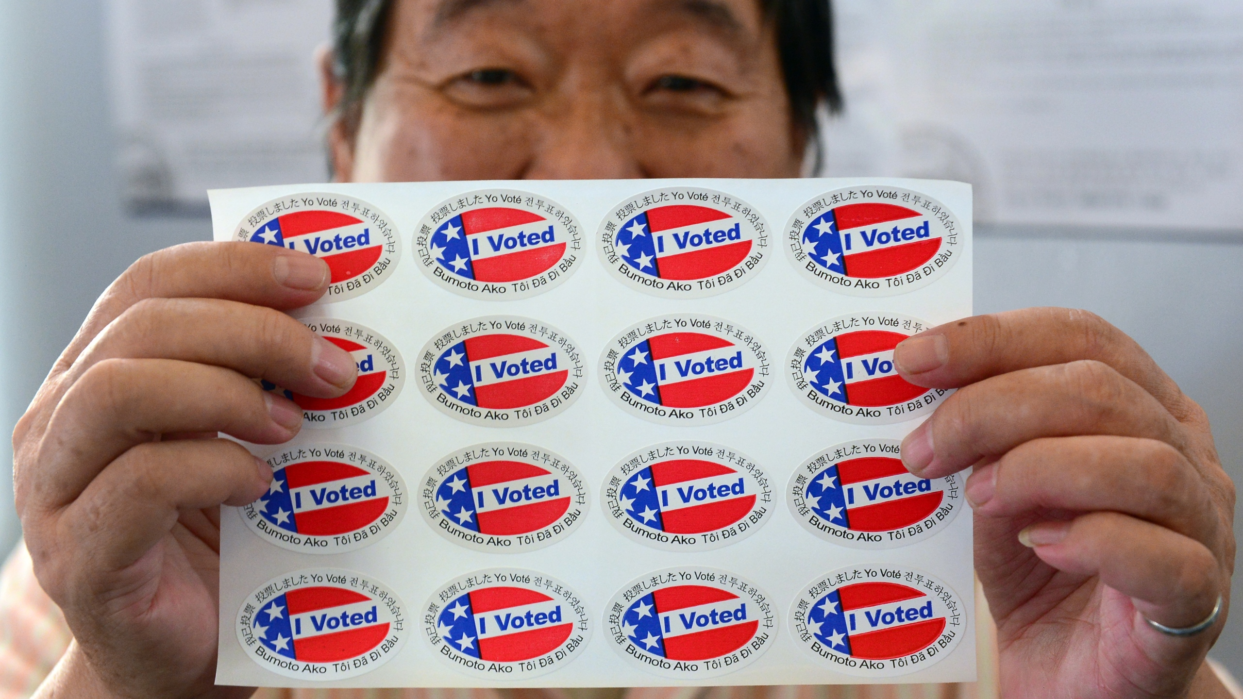 "Election official Henry Tung displays a sheet of ""I Voted"" stickers in various languages at a polling station at St. Paul's Lutheran Church in Monterey Park, Los Angeles County, on November 6, 2012. (Credit: FREDERIC J. BROWN/AFP/Getty Images)"